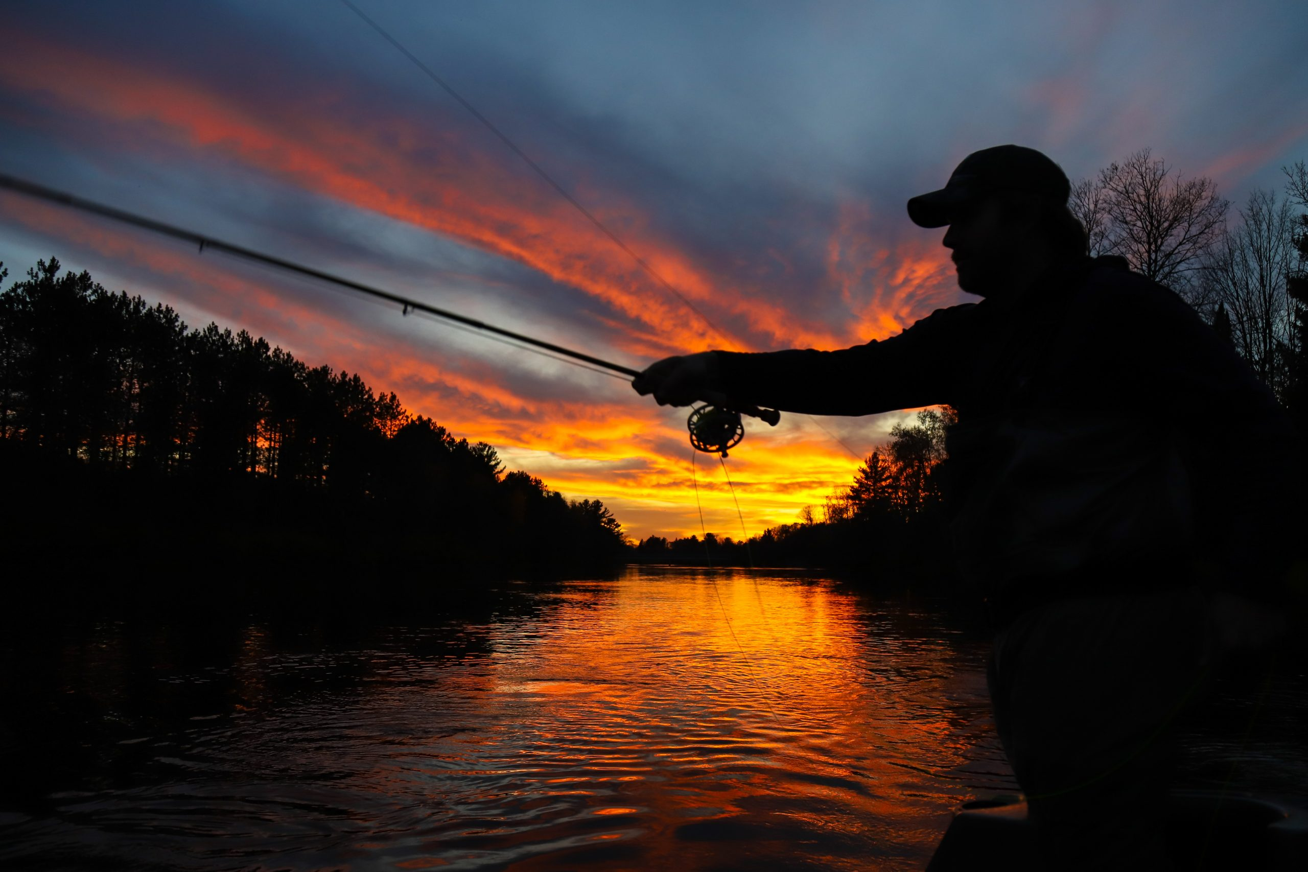 An image of a fisherman releasing a fish back into the Kenai River.